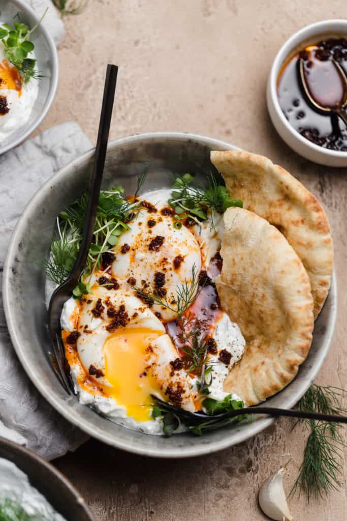turkish eggs with pita, herbed yogurt, and fresh herbs