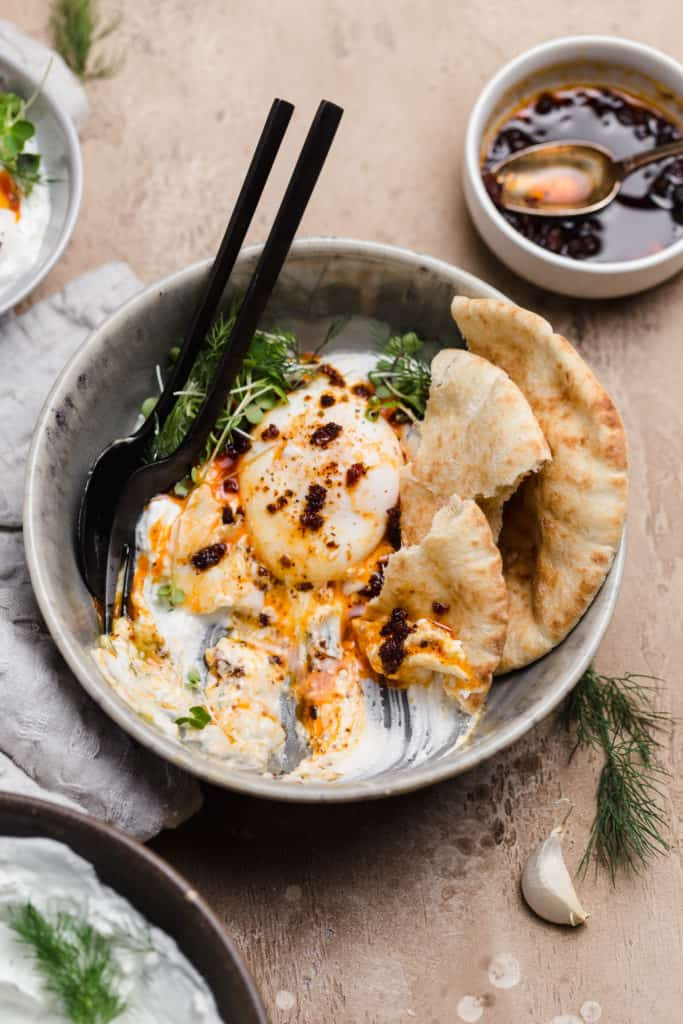 bowl of half eaten turkish eggs with pita and herbed yogurt