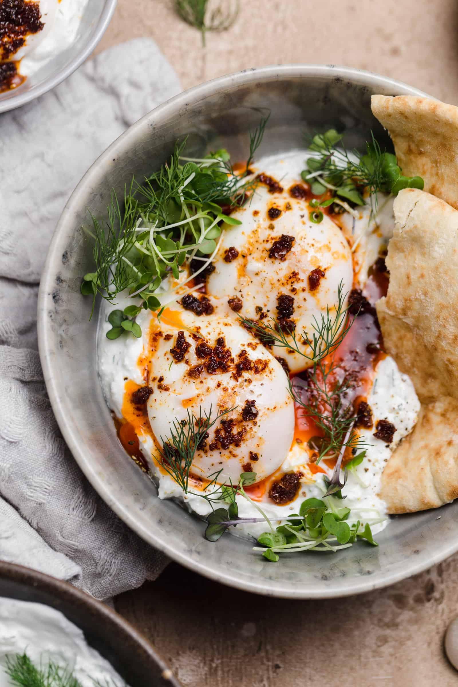 poached eggs with n'duja on top of herbed yogurt