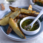 roasted potato wedges on a plate with a bowl of chimichurri