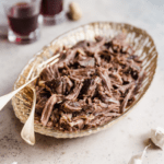 Shredded beef short ribs in a serving dish with two glasses of red wine