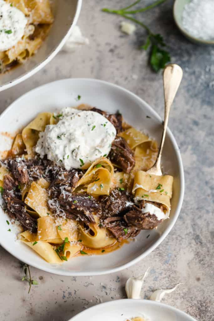 pappardelle with braised short ribs twirled around a fork