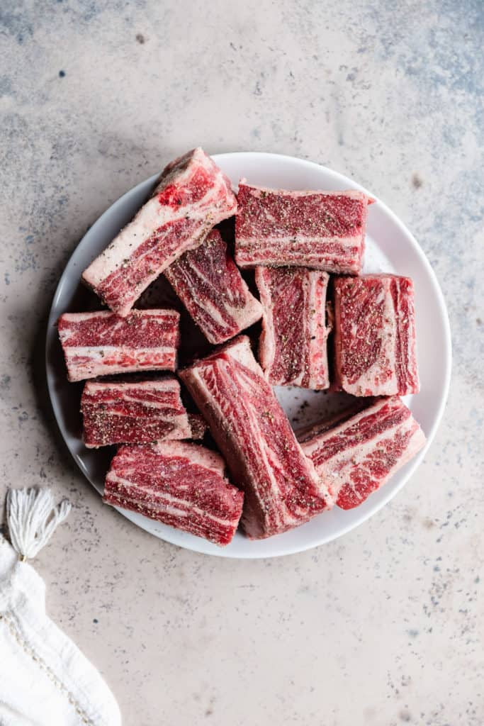 bone-in beef short ribs with salt and pepper before cooking