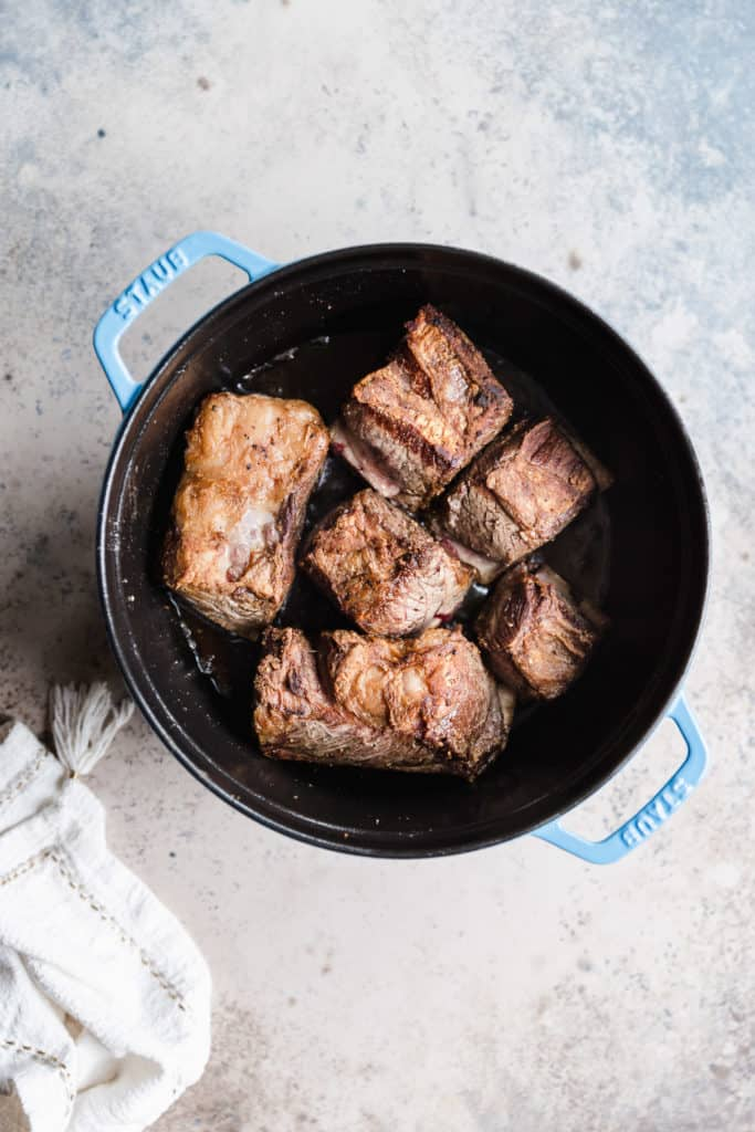 seared bone-in beef short ribs in a staub dutch oven
