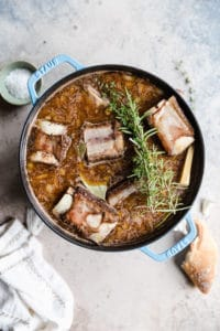 seared beef ribs in a dutch oven with beef broth, white wine, and fresh herbs