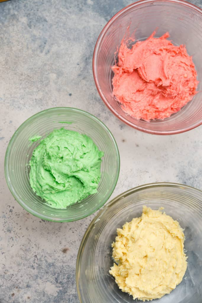 italian rainbow cookie batter divided into 3 mixing bowls, one for red, green, and yellow cookie dough