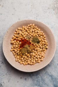 Rinsed and drained chickpeas with spices in a bowl