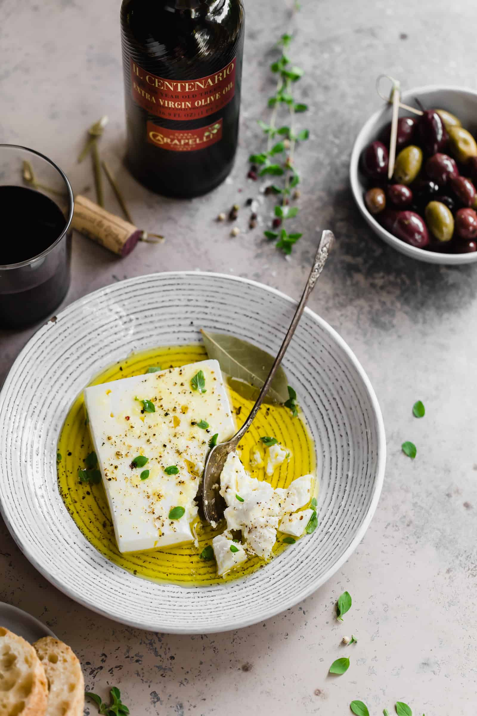 Marinated block of feta in bowl with extra virgin olive oil and fresh herbs