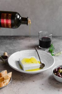 block of feta in bowl with extra virgin olive oil being drizzled on top
