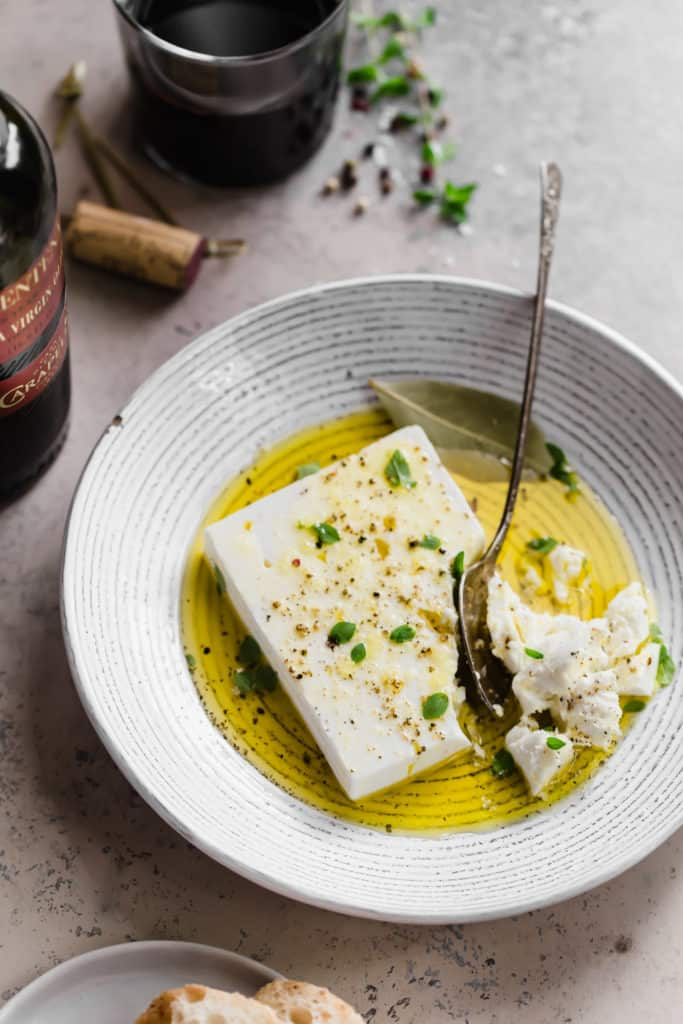 marinated feta with extra virgin olive oil in a white bowl