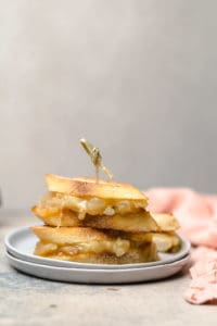 stacked mini grilled cheese sandwiches with brie held together by a toothpick