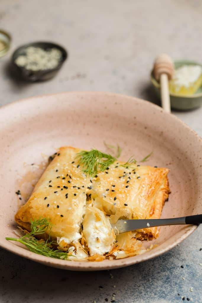 phyllo wrapped baked feta with sesame seeds and truffle honey in a bowl