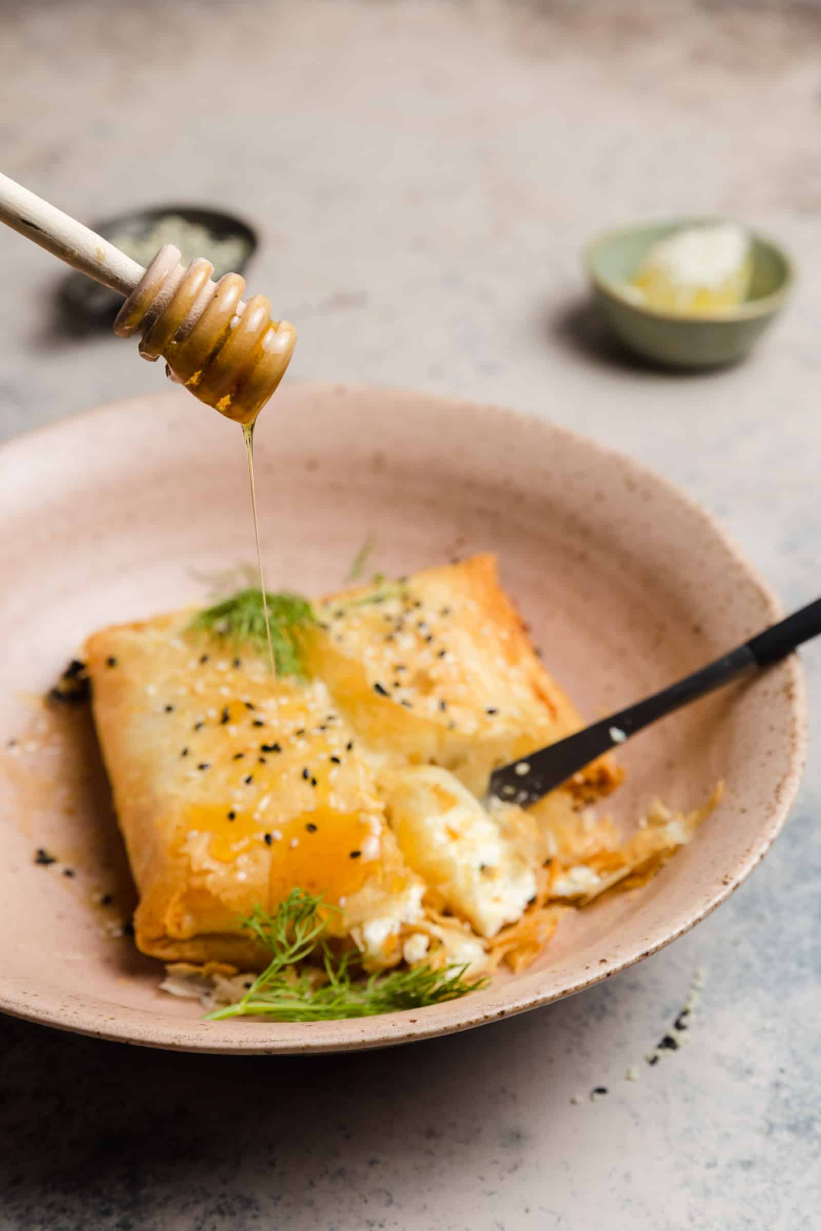 phyllo wrapped baked feta with sesame seeds, honey, and dill in a bowl
