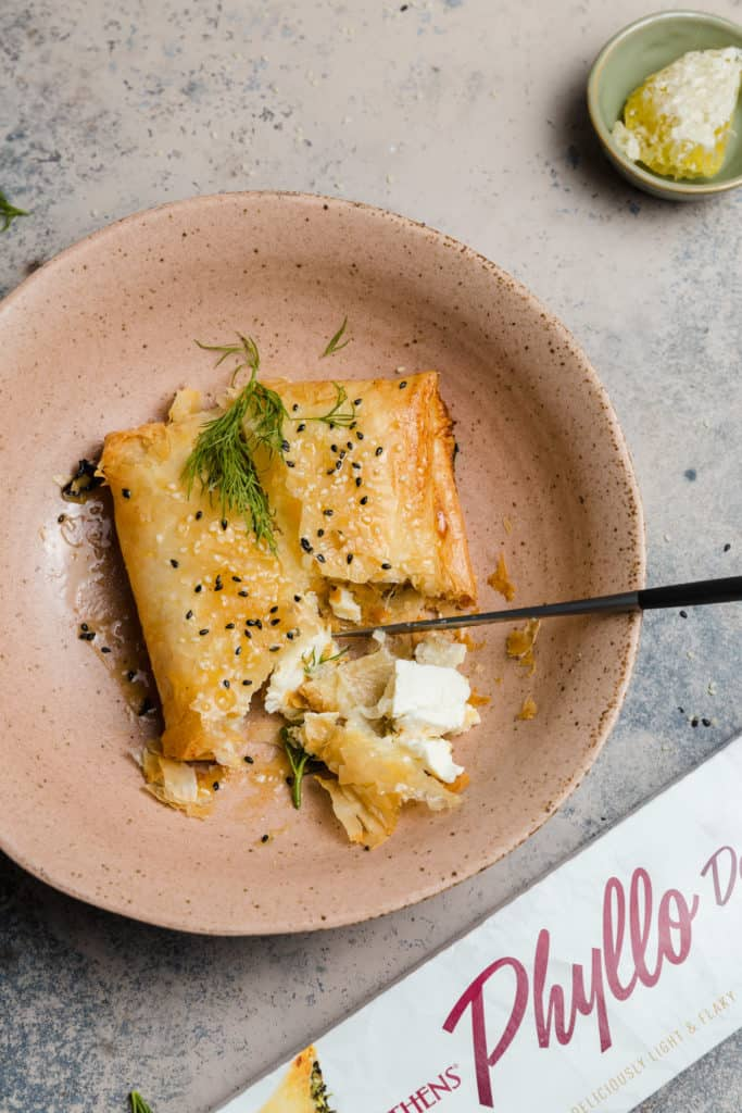 crispy phyllo-wrapped feta in a bowl with truffle honey, sesame seeds, and fresh dill