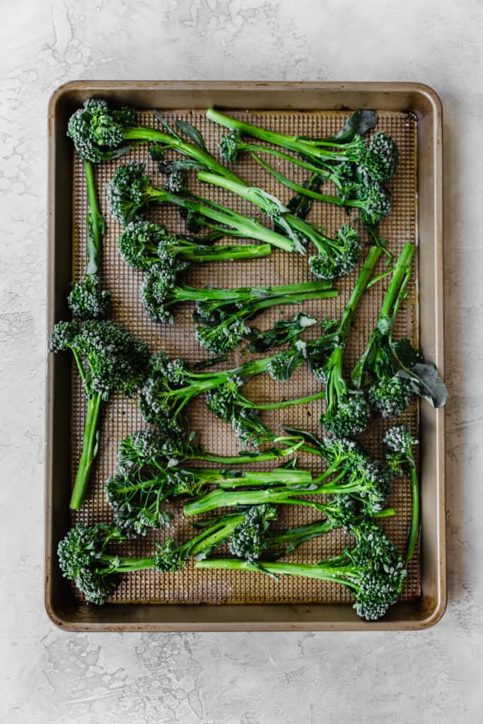 trimmed broccolini on a baking sheet