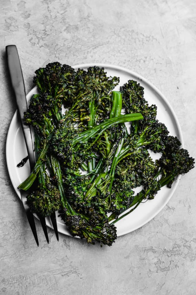 cooked roasted broccolini on a white plate