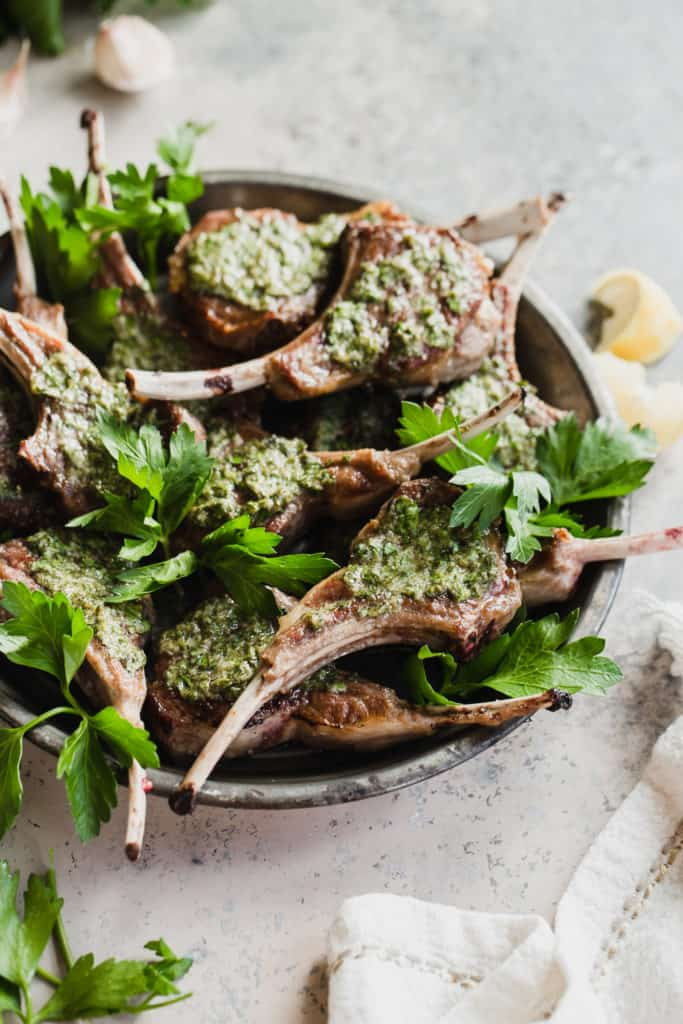 platter of seared lamb rib chops with herb sauce and parsley
