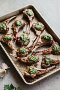 pan-seared lamb chops on baking sheet with herb sauce