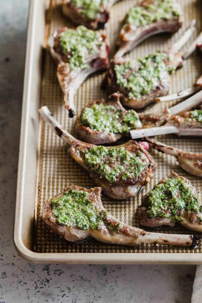 close-up of individual seared lamb chops with parsley sauce