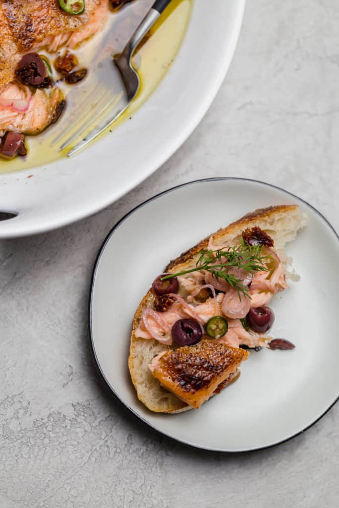 salmon escabeche on top of sliced bread