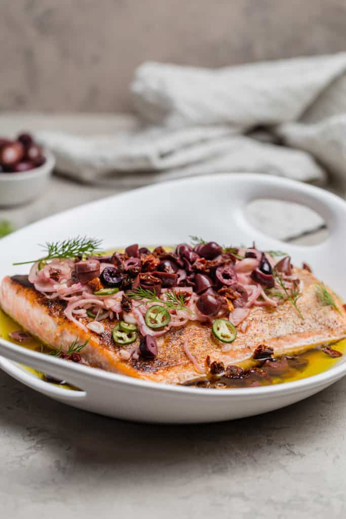 fish escabeche with olives and sun dried tomatoes in a white serving bowl