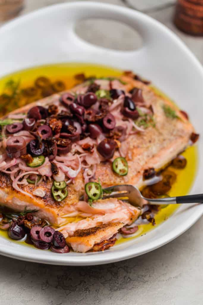 flaky fish escabeche in bowl with olives and sun dried tomatoes