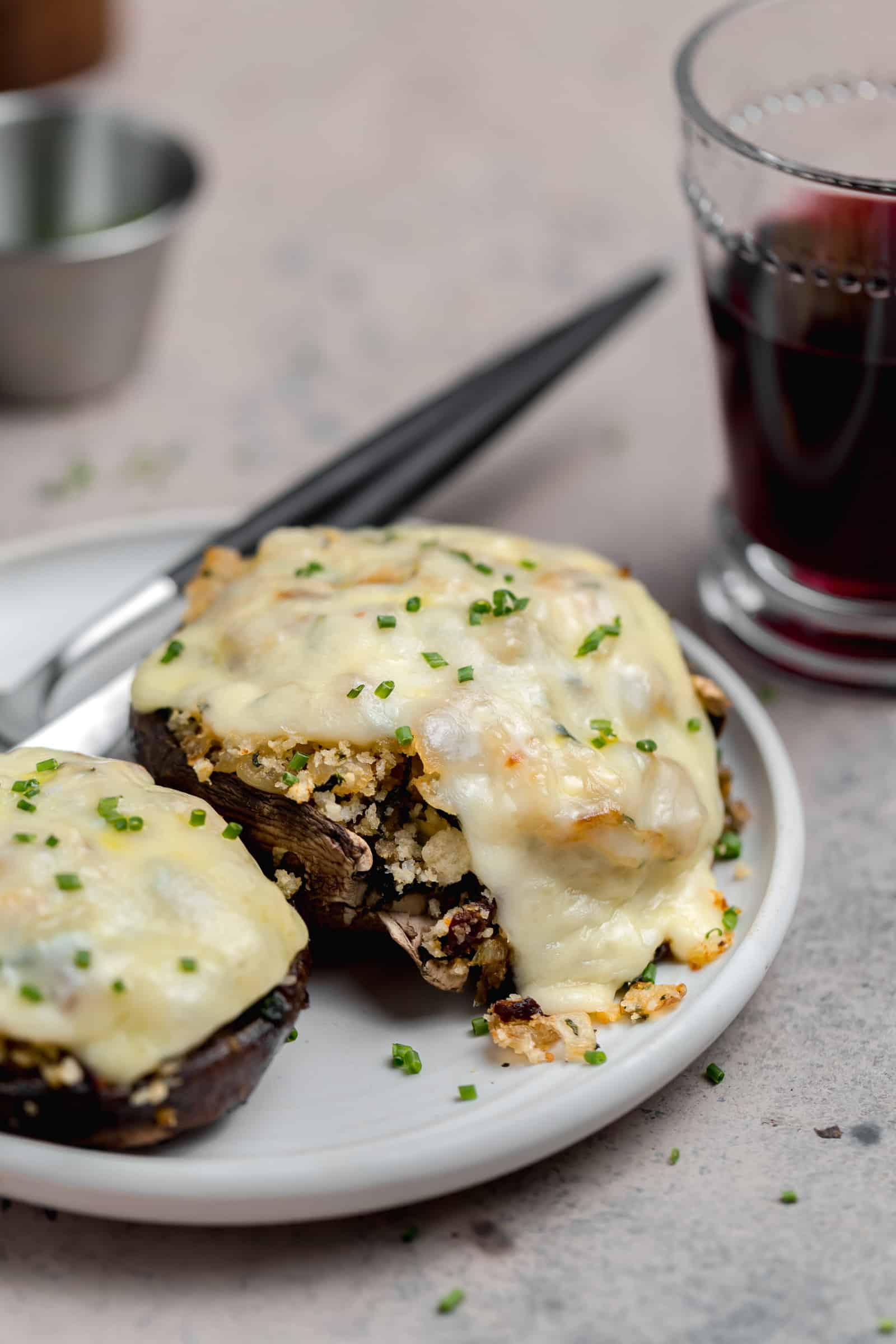 stuffed portobello mushroom caps with fontina on a white plate