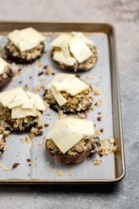 cheese on top of stuffed mushrooms on a baking sheet