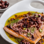 salmon escabeche in a white dish with olives and sun dried tomatoes