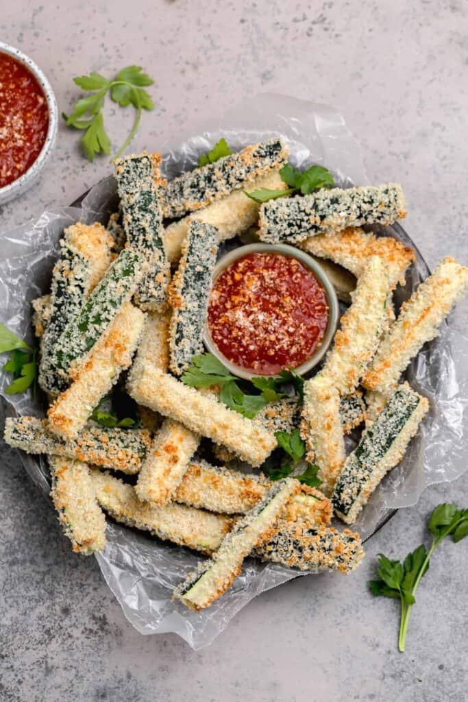 panko coated zucchini fries on a tray with marinara sauce
