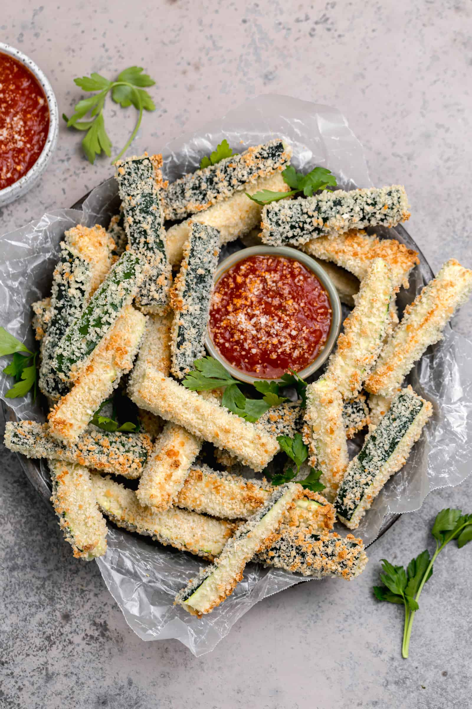baked zucchini fries with panko breadcrumbs on a tray with marinara sauce