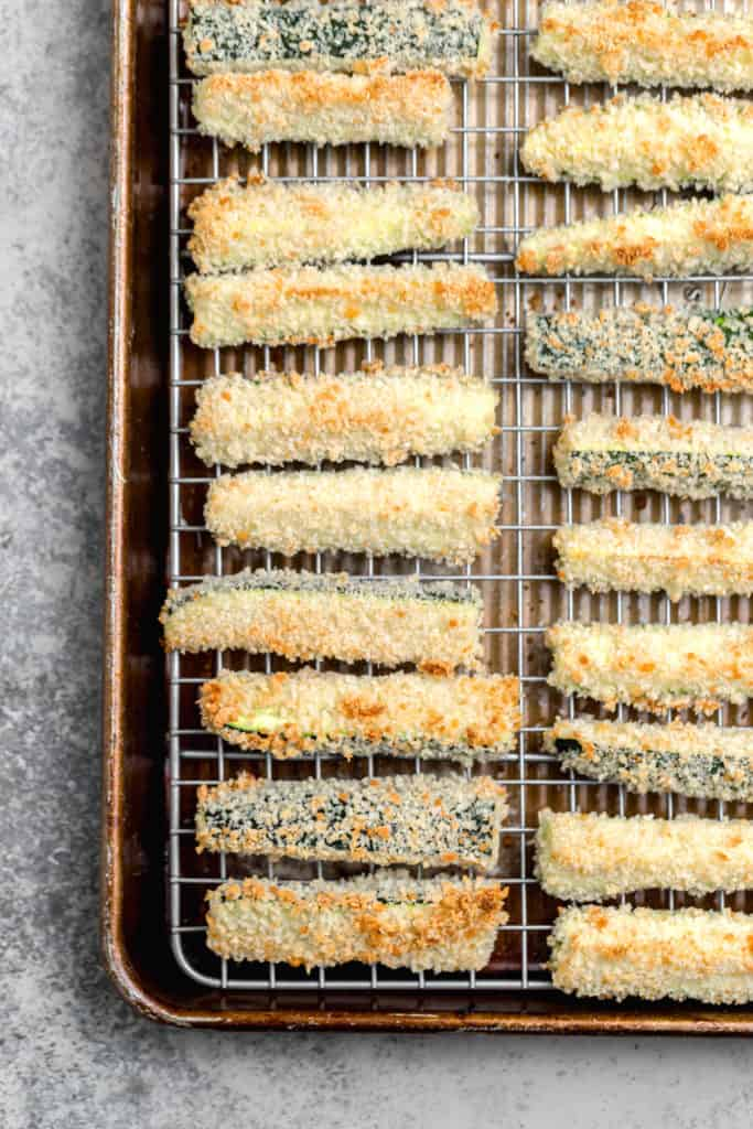 A close up of baked zucchini fries with panko breadcrumbs