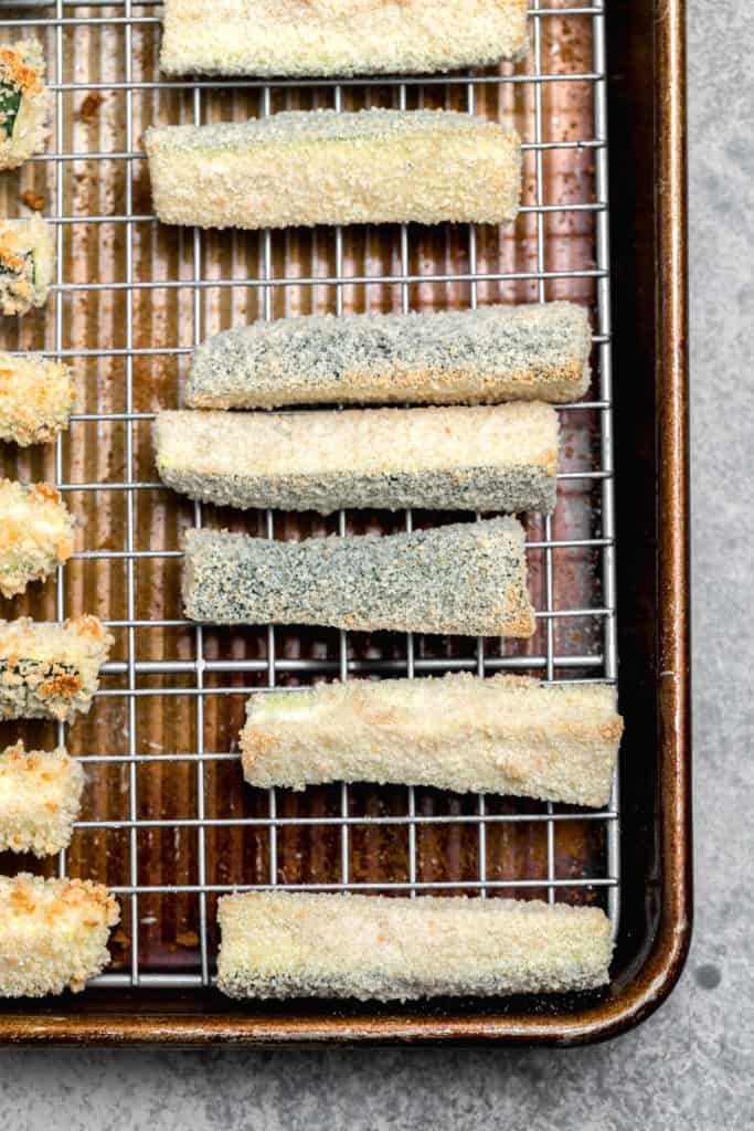 baked zucchini fries with breadrumbs on a wire rack