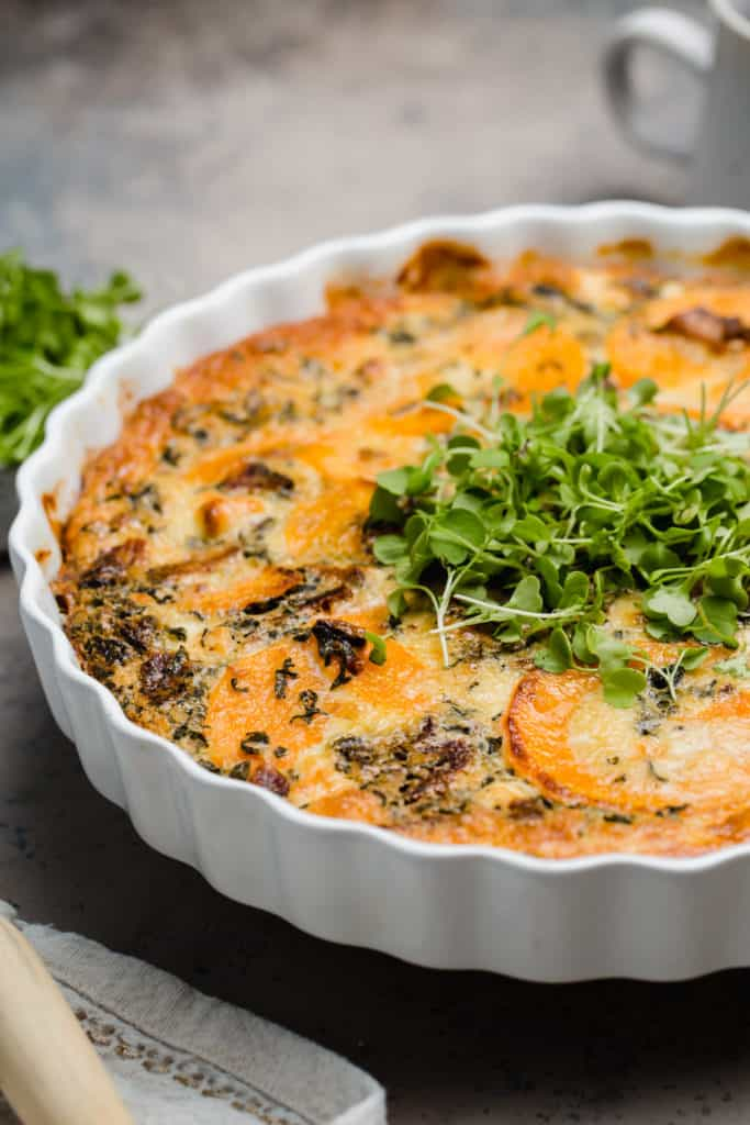 close up of baked goat cheese and butternut squash quiche with micro greens on top