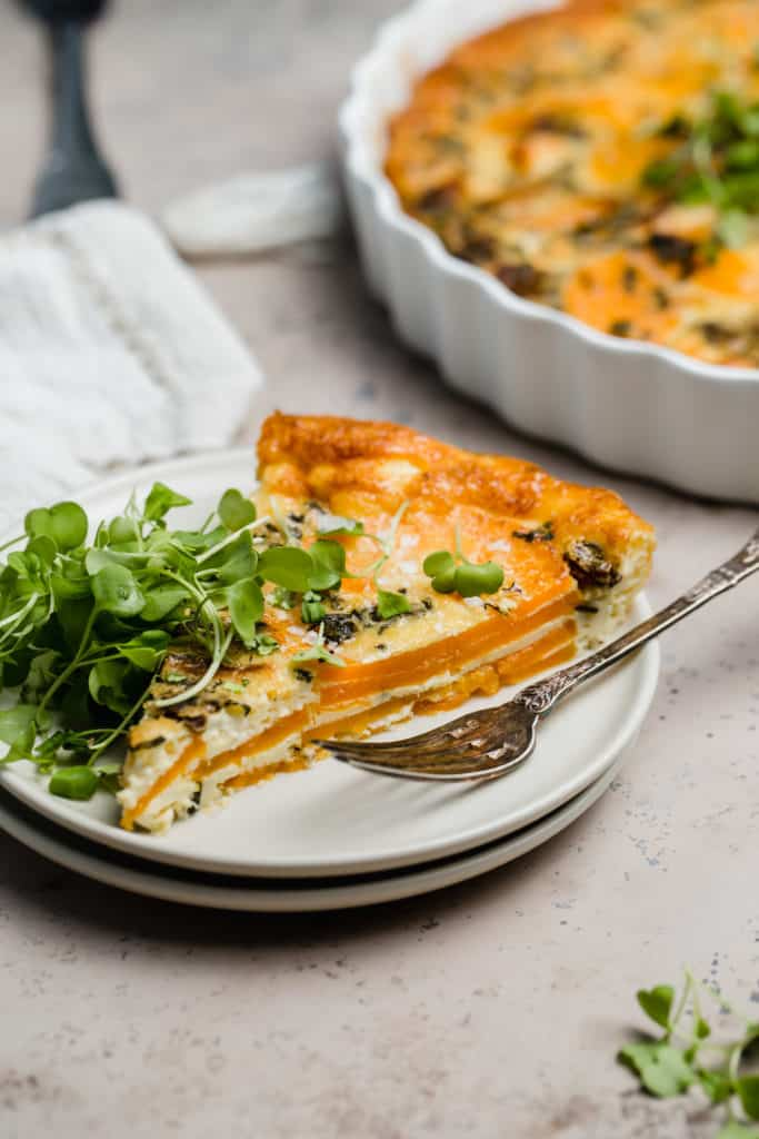 slice of goat cheese quiche with butternut squash on a plate with a fork