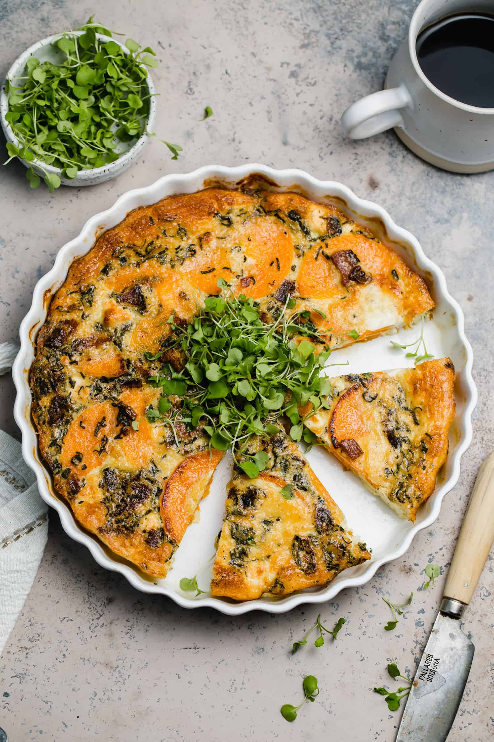 cooked goat cheese quiche with arugula microgreens in a white tart pan