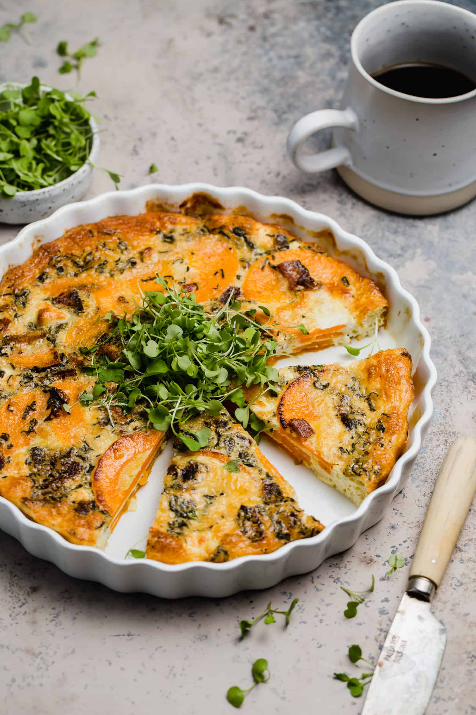 sliced butternut squash and goat cheese quiche in a tart pan with arugula microgreens