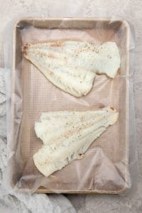 baked cod on a rimmed baking sheet