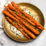 tandoori roasted carrots on a gold plate with herbed yogurt