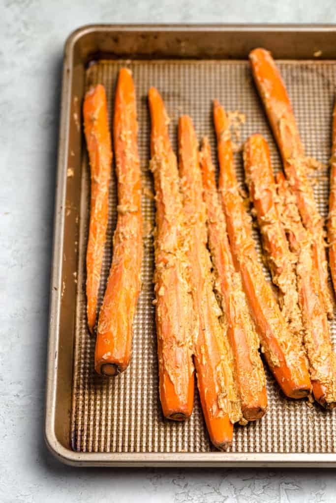 yogurt rubbed tandoori carrots on a baking sheet