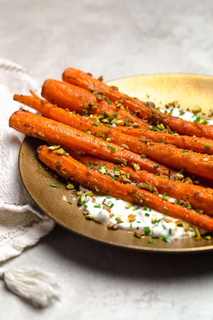roasted carrots on a plate with herbed yogurt and pistachios