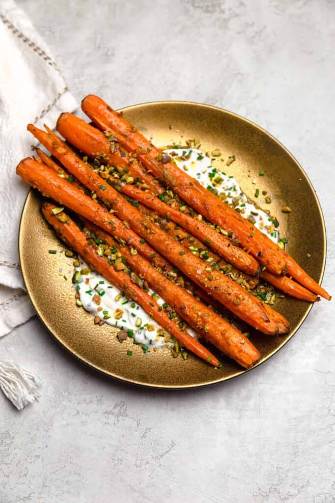 roasted carrots on a plate with yogurt and crushed pistachios