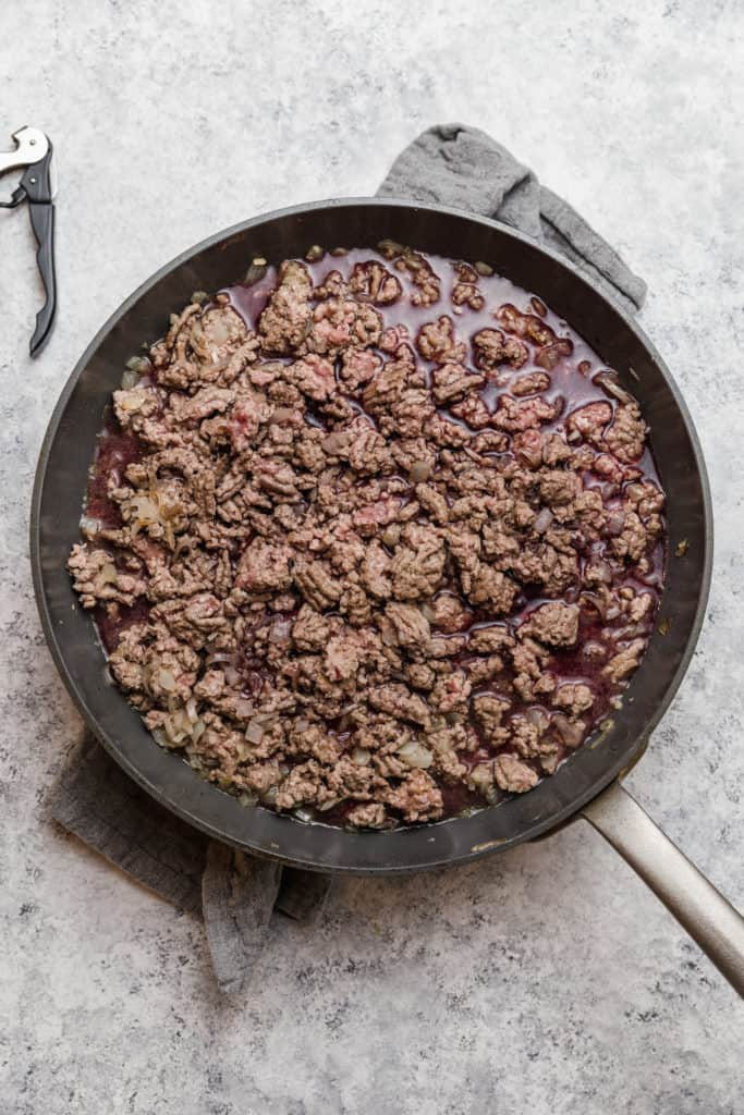 ground lamb cooking with red wine in a skillet
