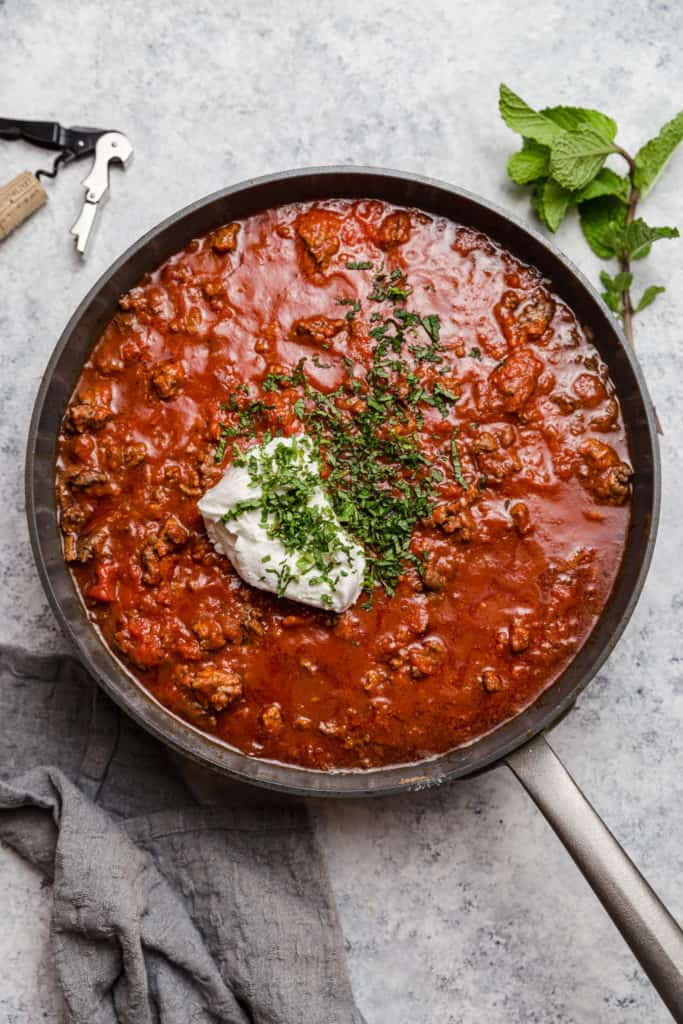 ground lamb ragu with mint and ricotta in a skillet