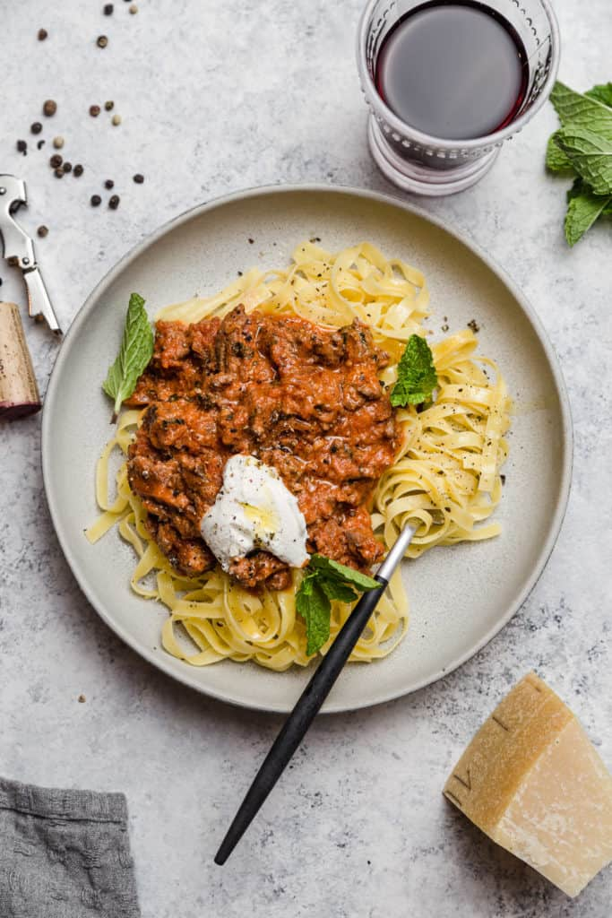 lamb ragu over tagliatelle on a plate with fresh ricotta