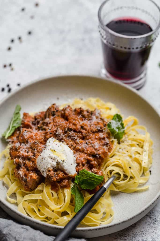 lamb ragu and fresh ricotta with mint over pasta on a grey plate