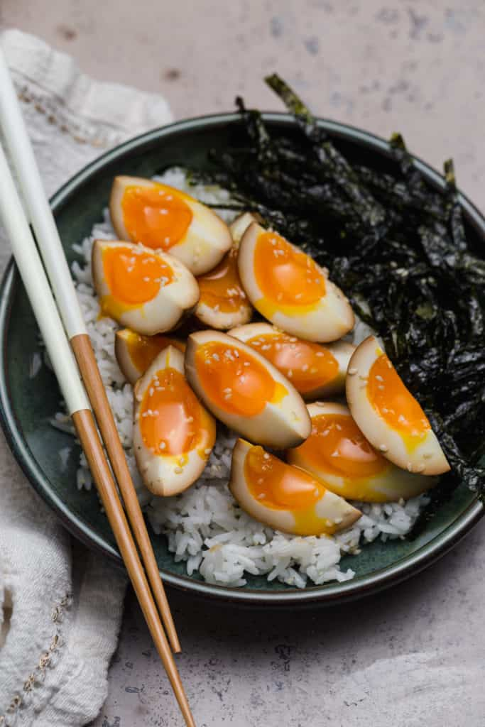 soy sauce eggs on top of sticky rice with seaweed