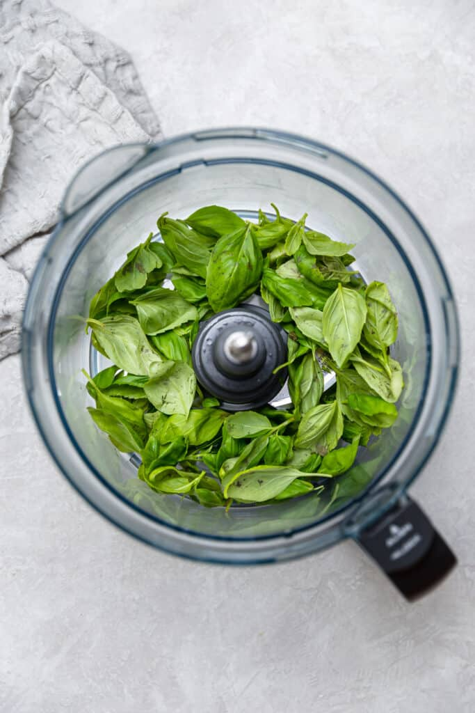 fresh basil in a food processor bowl
