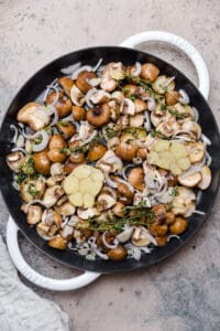 mushrooms, shallots, garlic, and thyme in a pan before roasting