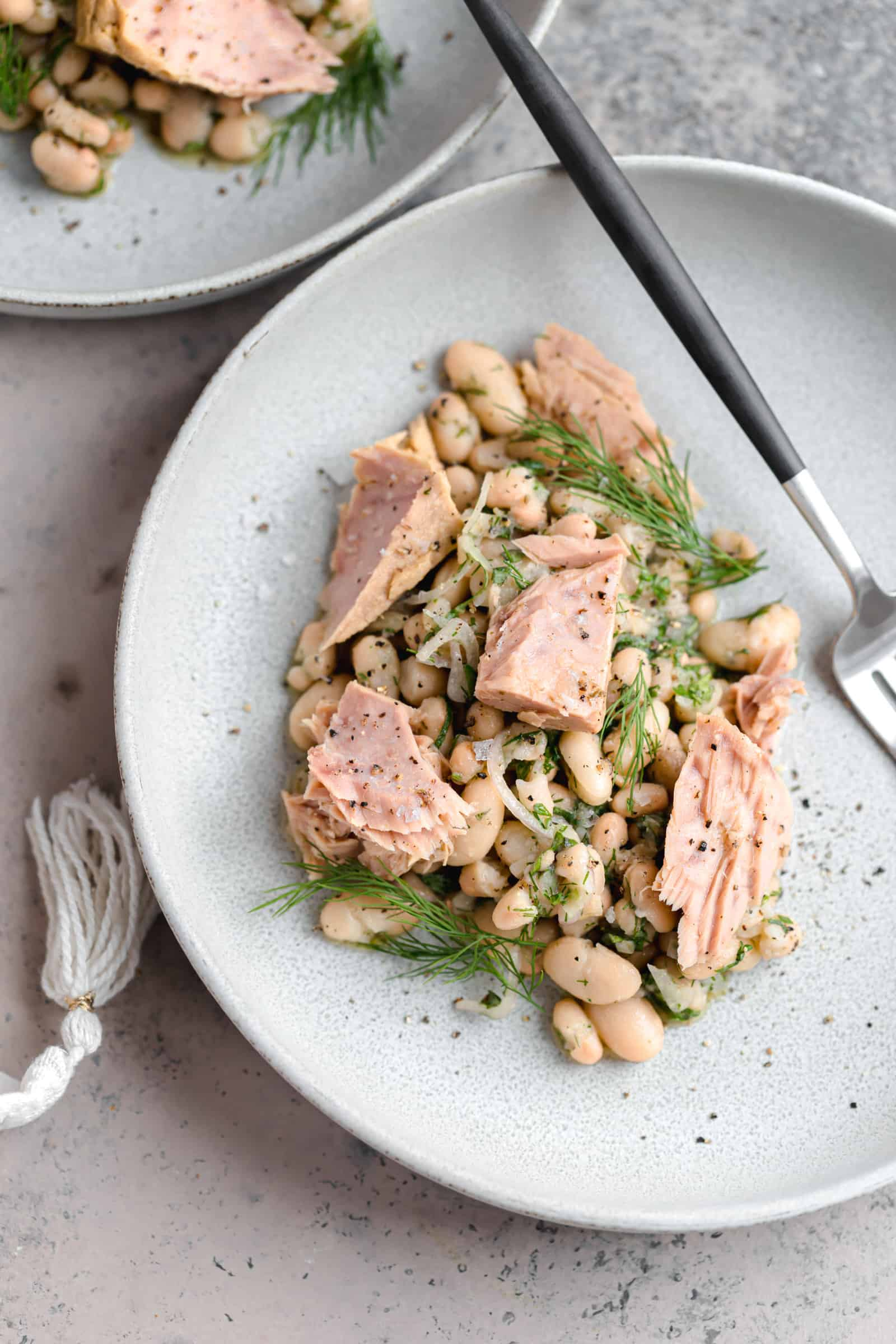 marinated white beans with tuna and dill on a gray palte